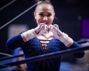 Kalyany Steele makes a heart with her hands at UCLA's meet against Oregon State in 2020